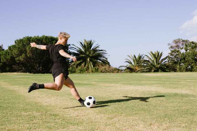 woman in black t shirt and black shorts playing soccer